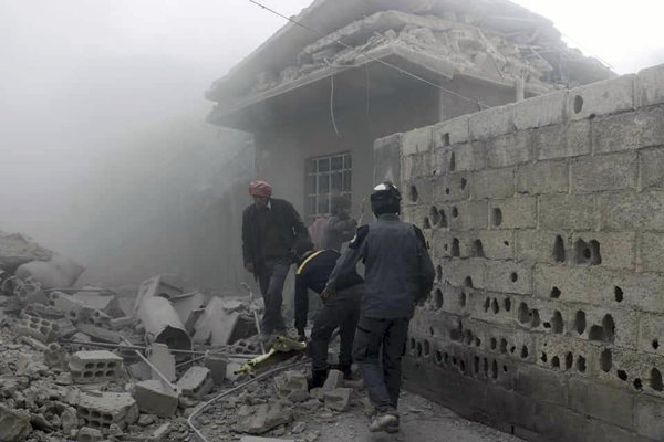 Členovia Sýrskej civilnej obrany Biele helmy a civilisti pátrajú po preživších po leteckých útokoch v Ghúte.