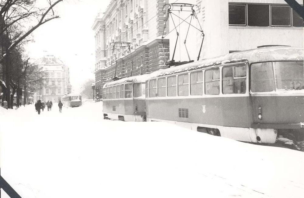 Zaviate električky na Jesenského, na úrovni Komenského ulice. Hore vzadu terajšie veľvyslanectvo USA (Kozičov dom) a Slovenské národné divadlo a jeho prístavba po pravoboku električky.