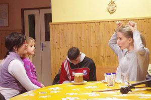 Adela Vinczeová radí Slávke, ako má vyzerať maska pračlovečky, že si treba dať do vlasov veľkú kosť.