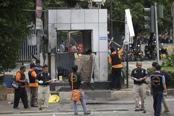 Policajní dôstojníci skúmajú trosky po výbuchoch a streľbe v centre indonézskej Jakarty.