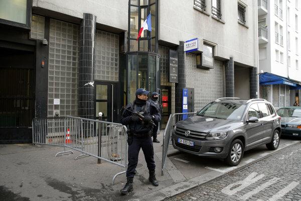 Policajti hliadkujúci pred policajnou stanicou v Paríži.