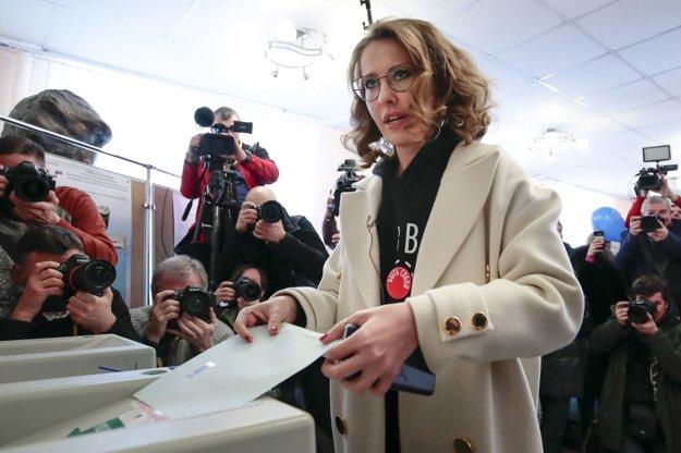 Prezidentská kandidátka Xenia Sobčaková hádže volebné lístky vo volebnej miestnosti v Moskve.