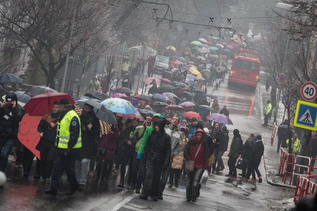 Účastníci protestu pochodujúci pred parlament.
