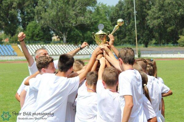 Pohár je v správnych rukách. Tešia sa z neho mladší žiaci FKM Nové Zámky aj so svojim trénerom.