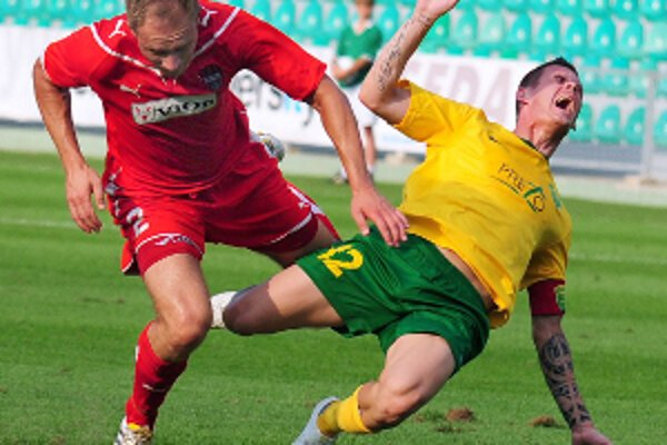 V 1. kole Corgoň ligy hral majster MŠK Žilina na domácom trávniku s nováčikom ligy FC ViOn Zlaté Moravce. Na snímke hráč Zlatých Moraviec Milan Pavlovič (vľavo) fauluje kapitána domácich Róberta Ježa.