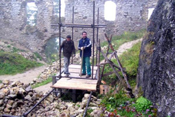 Dobrovoľníci pracujúci na čistení studne na hradnom nádvorí.