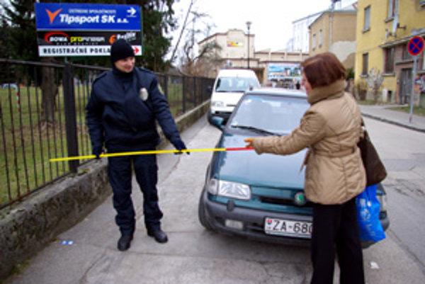 Mestský policajt meria voľný priestor na chodníku ulice J. Kalinčiaka.