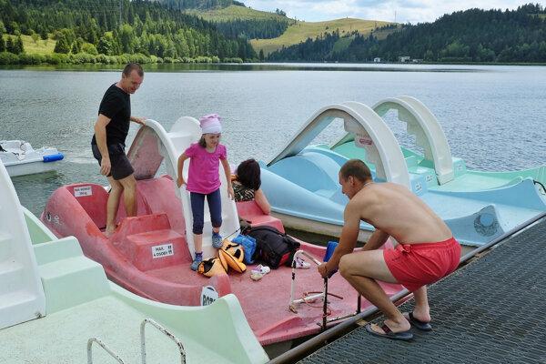 Na snímke plavčík pomáha dovolenkárom vystúpiť z vodných bicyklov na priehrade Palcmanská Maša v Národnom parku Slovenský raj.