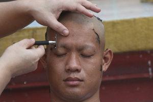 Člen thajského futbalového tímu Chanin Vibulrungruang počas holenia hlavy v rámci budhistického ceremoniálu