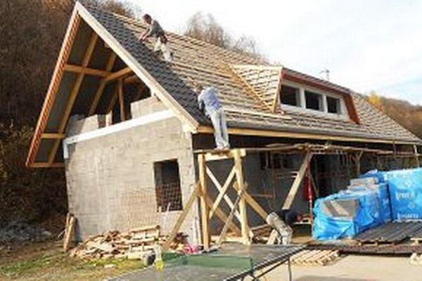 Pracovníci dokončujú pokrytie strechy.