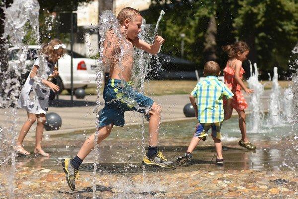 Chlapec šantí vo fontáne v centre mesta počas horúceho letného dňa v Piešťanoch.