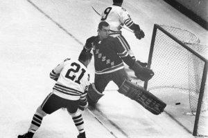 Stan Mikita (číslo 21) prekonáva v novembri roku 1965 brankára New York Rangers Eddieho Giacomina.