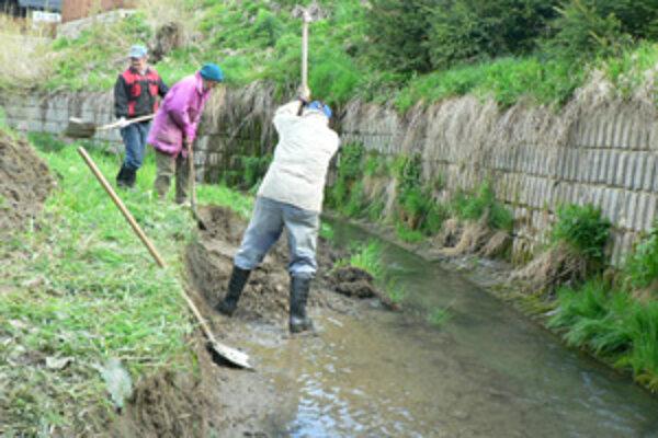 Obec s aktivačnými pracovníkmi čistí koryto potoka, aby ho spriechodnila a zabránila prípadným povodniam.