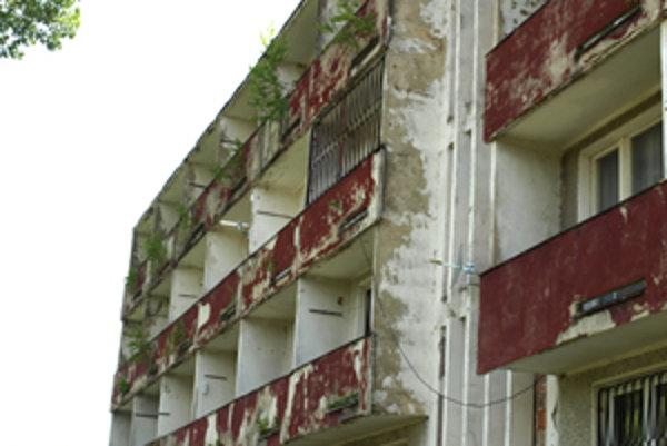 Rozpadávajúce sa balkóny zarastajú stromami. Budova je v dezolátnom stave.
