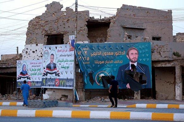 Bilbordy strán na parlamentné voľby sú na zničených budovách po bojoch medzi irackými vládnymi silami a militantmi Islamského štátu v meste Ramádí, 115 kilometrov západne od Bagdadu, 11. mája 2018.