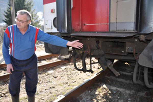 Bývalý železničiar Igor Macák ukazuje na vytrhnuté ťahadlové ústrojenstvo vozňa.