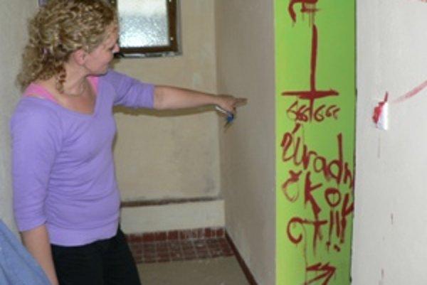 Oravskoporubčanka Katarína Kutlíková ukazuje popísanú stenu v zborovom dome. Z konania vandalov je zhrozená.