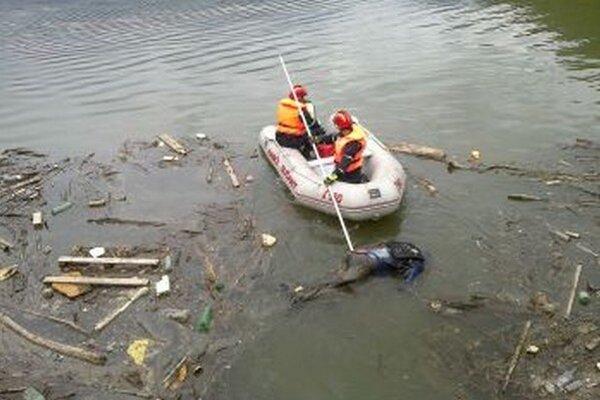 Hasiči vyťahujú mŕtveho muža z vody.