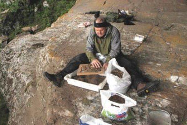 Ján Obuch pri práci v teréne vysoko na skale.