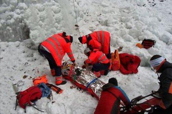 Záchranári pomáhajú zranenému lezcovi.