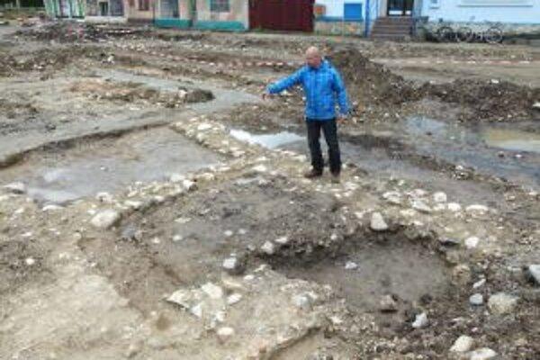 Archeológ Záhorec ukazuje nájdené kamenné základy meštiackeho domu.