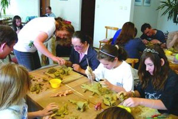 Vychovávateľka Ivka Ružinská pomáha deťom pri práci s hlinou.