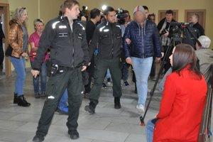 Policajti predvádzajú vodiča Porsche Cayenne (s kapucňou na hlave), ktorý spôsobil dopravnú nehodu, ku sudcovi.
