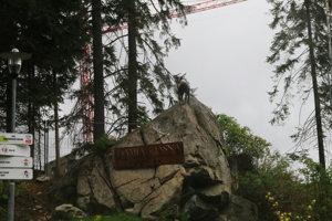 Tabuľa značiaca nový hotel. Nad ňou je socha kamzíka.