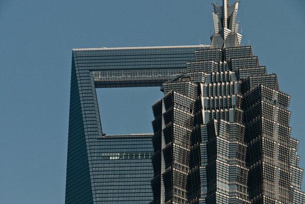 Adrenalínoví lezci sa na sociálnych sieťach chvália zdolaním mrakodrapu Jin Mao Tower, za ním sa vypína Shanghai World Financial Center.