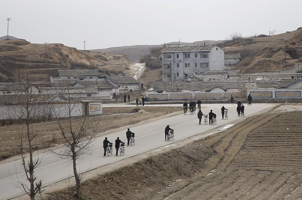 Severokórejčania tlačiaci bicykle pozdĺž cesty.