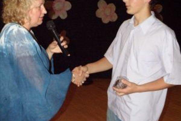 Riaditeľka ZŠ Slovenských partizánov v Pov. Bystrici Iveta Štiborová oceňuje najlepšieho žiaka školy Samuela Kecíka.