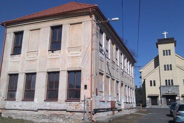 Pamätná škola stojí vedľa evanjelického kostola.