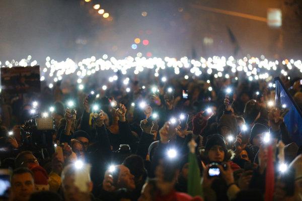 Protivládni demonštranti svietia mobilmi počas protestu 16. decembra v Budapešti.