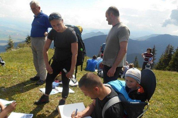Účastníci sa na vrchole poludnice zapísali do výstupovej knihy.