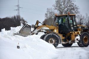 Nakladač odhŕňa snehové záveje na ceste pred obcou Ladmovce.