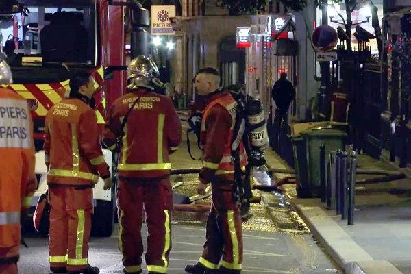 Parížski hasiči pri zásahu pred horiacou budovou.
