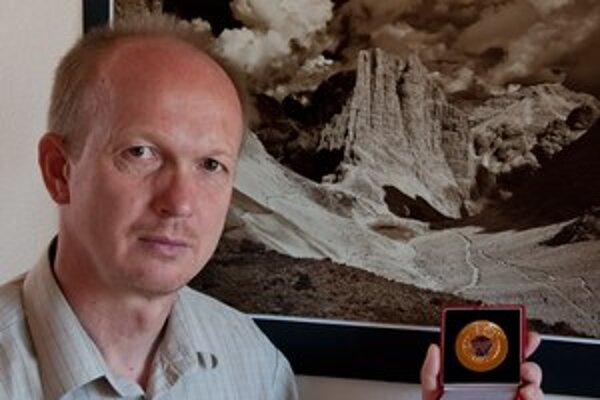 Vladimír Vlček s medailou a v pozadí s fotografiou, ktorá mu zlato priniesla.