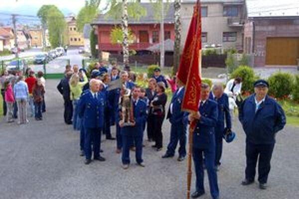 Likavskí hasiči s historickou zástavou a sochou svätého Floriána pred kostolom.