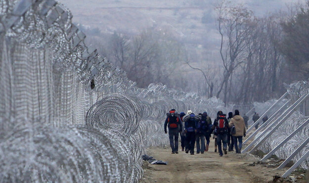 Utečenci, ktorí prekročili macedónske hranice  nelegálne, kráčajú medzi ostnatými drôtmi.