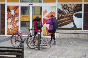 Stojan na bicykle pred potravinami na pešej zóne.