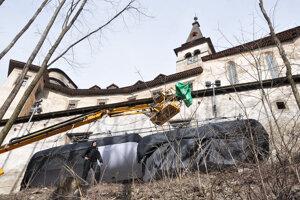 Balóny pod hradnými múrmi stráži muž včiernom. Využili ich na vytvorenie mesačného svitu.