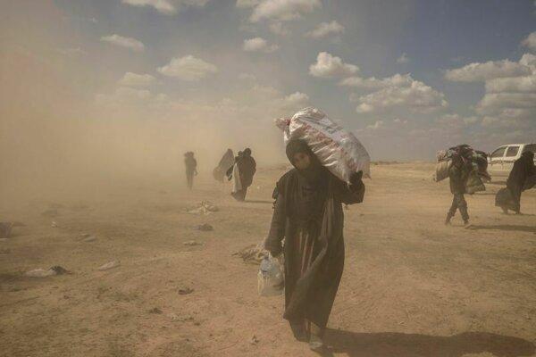 Žena nesie zásoby jedla v poslednom území ovládanom Islamským štátom v obkľúčenej enkláve Bághúz vo východnej Sýrii.