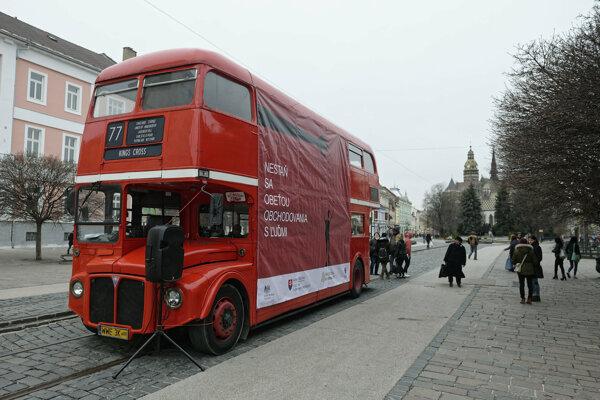 Červený poschodový autobus upozorňuje na problém obchodovania s ľuďmi.