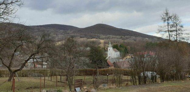 Kostol v Rožňavskom Bystrom. Z hôr v pozadí vyteká povestný prameň.