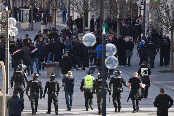 Policajti usmerňujú skupinu fanúšikov.