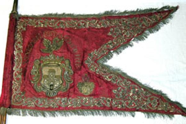 Zástava je vyhotovená z červenej tkaniny a po obvode má zlatými niťami bohato vyšívané rastlinné ornamenty.