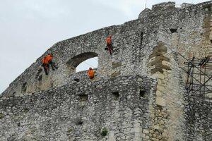Múry západných palácov Spišského hradu sanujú horolezci.