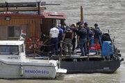Potápač (uprostred) sa pripravuje na skok do Dunaja počas záchrannej akcie v Budapešti.