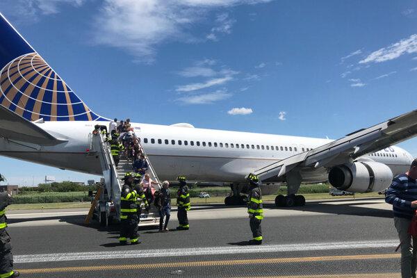 Požiarnici pomáhajú cestujúcim z lietadla.