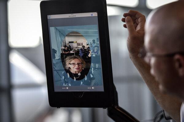 Manažér stanice Chad Shane (vpravo) z aerolínií SAS uvádza na palubu cestujúcu skrz biometrický systém rozpoznávania tváre, ktorý predstavili v Dulles vo Virgínii 6. septembra 2018.